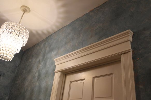 heavy paneled wooden recycled door and molding on my blue venetian plaster walls